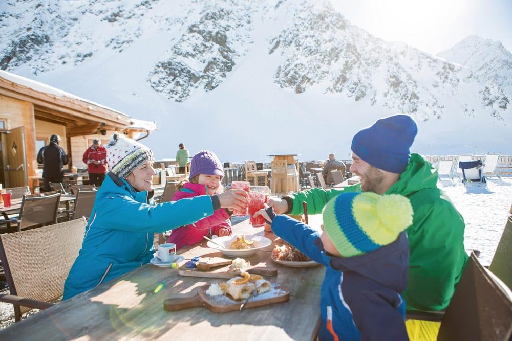 Eine Familie sitzt vor einer Skihütte