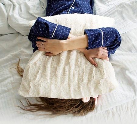 Person versteckt sich im Kissen