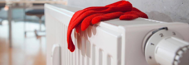 Rote Handschuhe auf Heizkörper