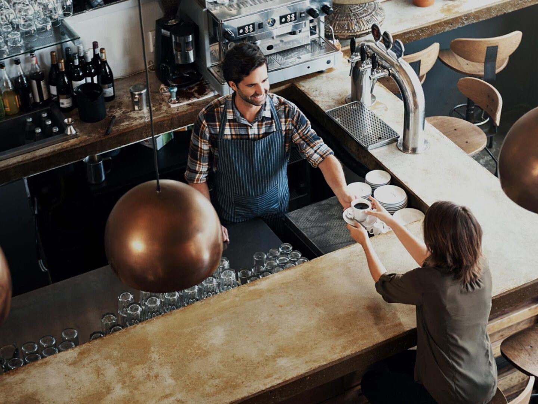 Mann am Tresen gibt Kaffee an Kunden
