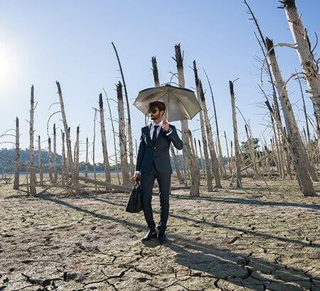 Mann mit Schirm in trockener Landschaft