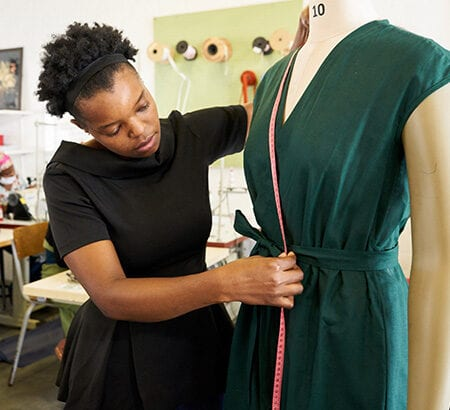 Frau schneidert Kleid und legt Maßband an