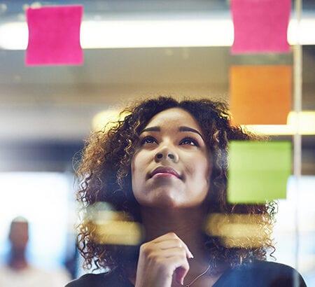Junge Frau schaut hoch zu Post-It Notizen