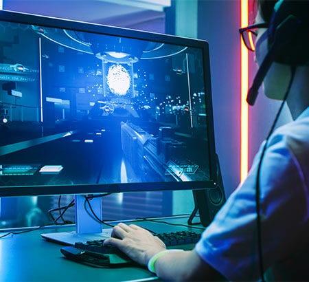 Mann sitzt am Computer und macht E-Sport