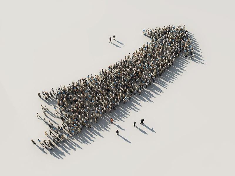 Menschen versammeln sich zu einem Pfeil nach oben