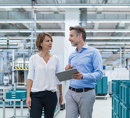 Frau und Mann laufen durch Produktionshalle