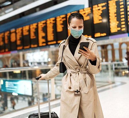 Frau am Flughafen mit Atemschutzmaske