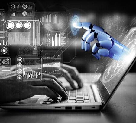 Hände arbeiten an einem Laptop, Roboterhand zeigt aus dem Bildschirm