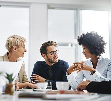Ein diverses Team sitzt zusammen am Tisch