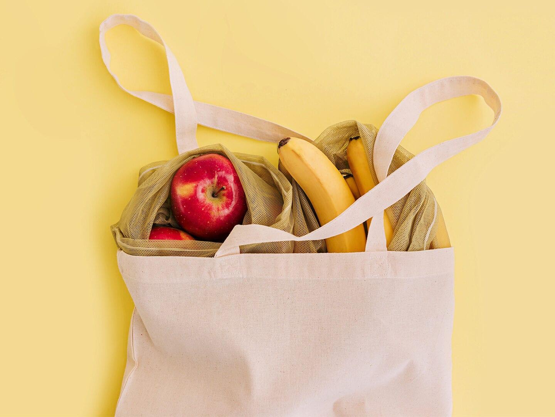 Einkaufstasche mit Obst auf gelbem Grund