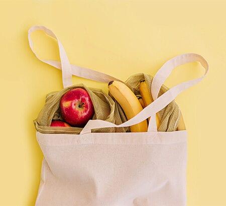 Einkaustasche mit Obst auf gelbem Grund