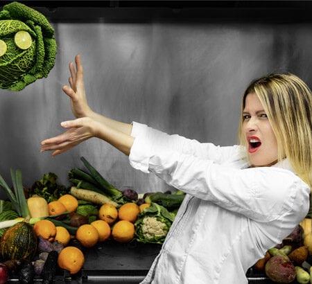 Köchin steht in der Küche und wirft mit Gemüse
