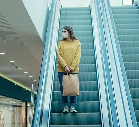 EIne Frau steht alleine auf einer Rolltreppe mit einer Atem-Schutz-Maske im Gesicht