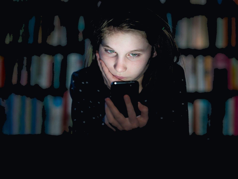 Ein Mädchen guckt gelangweilt auf ihr Handy