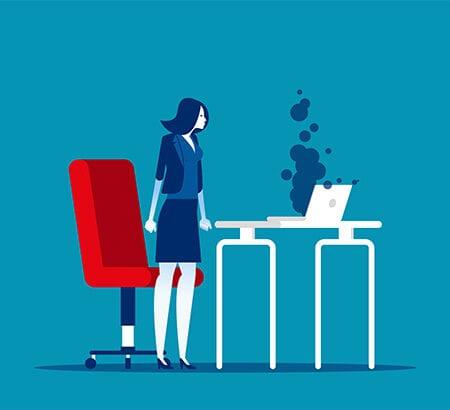Eine Frau ist aus ihrem Schreibtischstuhl aufgestanden und steht mit geballten Fäusten vor ihrem Schreibtisch, auf dem ein Laptop grauen Rauch absondert.
