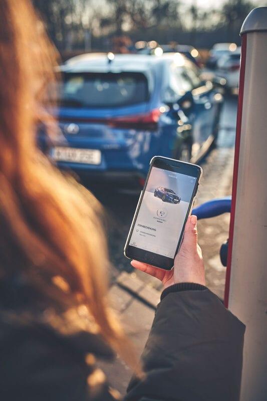 Eine Frau conected sich mit ihrem Lexus UX 300e durch die Lexus Link App