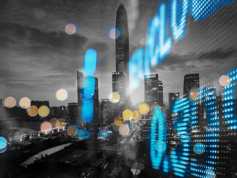 Aktienkurse spiegeln sich vor einer Skyline.