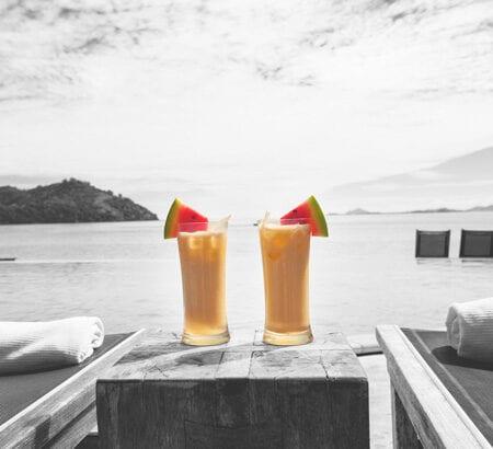 Zwei Cocktails stehen neben Sonnenliegen am Meer