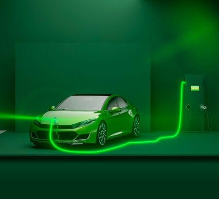 Ein grünes Auto ist durch ein grün leuchtenden Kabel mit einer Ladestation verbunden.