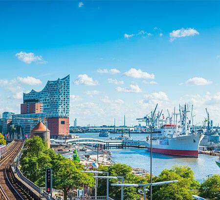 Links stehen Häuser und rechts ist ein Teil des Hamburger Hafens zu sehen. In der Mitte des Bildes fährt gerade eine Bahn entlang der Gleise und im Hintergrund steht die Elbphilharmonie. Der Himmel ist überwiegend blau mit vereinzelten Wolken.