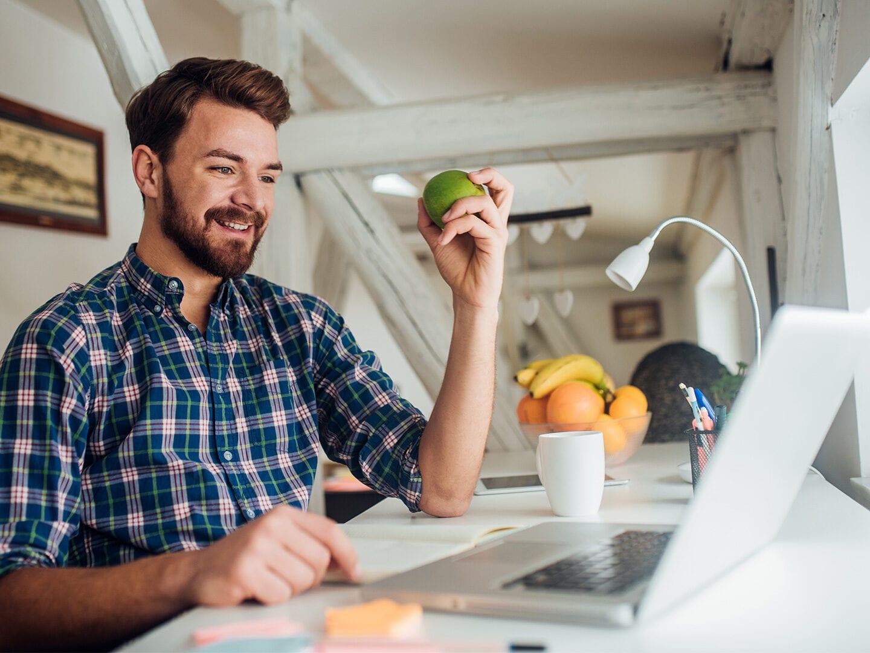 Ein Mann arbeitet im Homeoffice und isst dabei einen Apfel