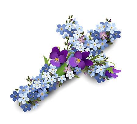 Das Bild offenbart ein religiöses Kreuz, das aus blauen, weißen und lilafarbenen Blumen bestückt ist.