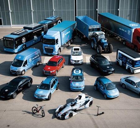Blick von oben auf einen Fuhrpark von ZF mit Pks, Lkw, Rennwagen, Fahrrad, Roller und Transportern, die alle einen E-Antrieb von ZF haben.
