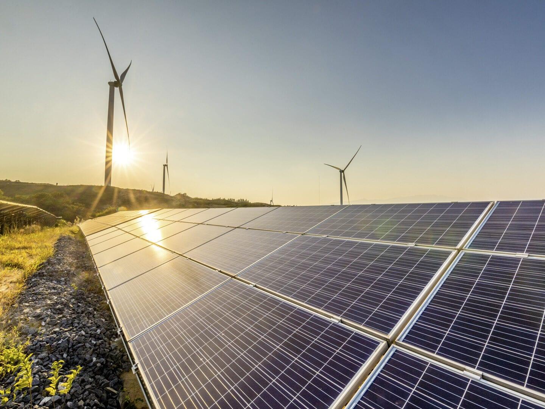 Nachhaltige Energie: Vorne rechts ist ein Solarpanel zu sehen, hinten links ein Windrad, hinter dem die Sonne untergeht.