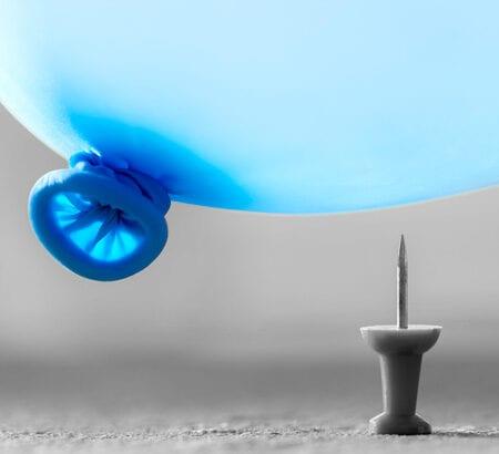 Ein Luftballon schwebt über einer Nadel.