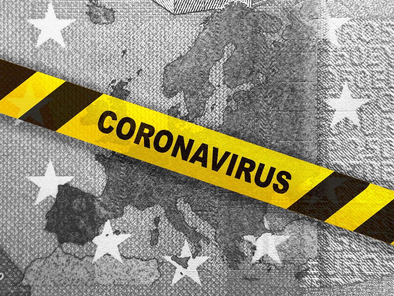 Eine Coronavirus-Warnung liegt über einem Geldschein.