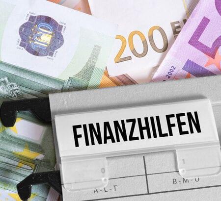Ein Ordner mit der Aufschrift Finanzhilfen liegt auf einem Geldstapel.