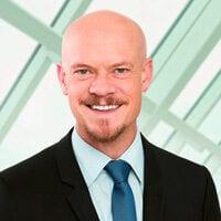 Portraitfoto von Per Protoschill von der Stuttgarter Lebensversicherung. Mann mit Glatze und Bart sowie Anzug und Krawatte.