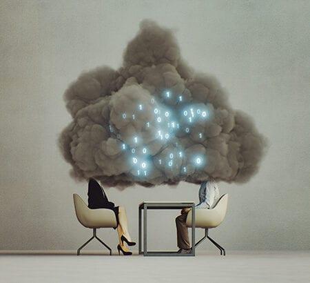 Zwei menschen an einem Tisch, deren Gesichter von einer Cloud mit Binärcode bedeckt sind