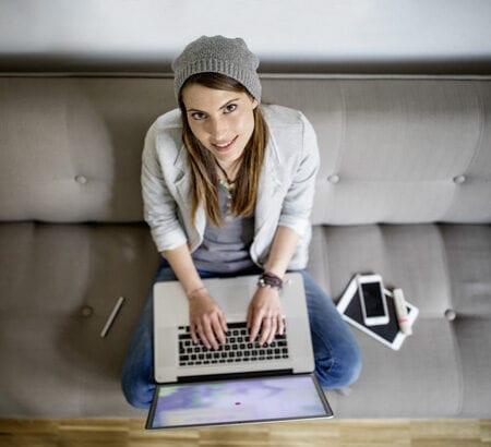 Ein Foto aus der Vogelperspektive, das eine Frau am Laptop zeigt, die auf dem Sofa sitzt
