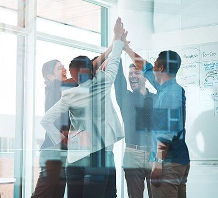 Eine Gruppe von Arbeitern klatschen sich im Büro gemeinsam ab