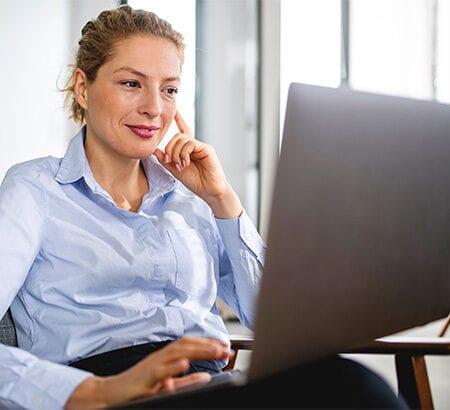 Frau sitzt vor dem Laptop und arbeitet