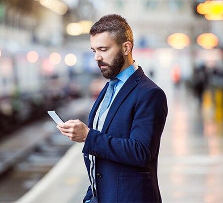 Mann mit Handy am Bahnhof