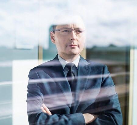 Business Mann schaut aus dem Fenster heraus
