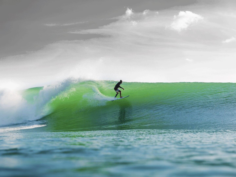 Ein Surfer auf einer grünen Welle.
