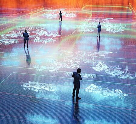 Vernetzung: Vier Menschen stehen auf einem Boden einer IT-Infrastruktur