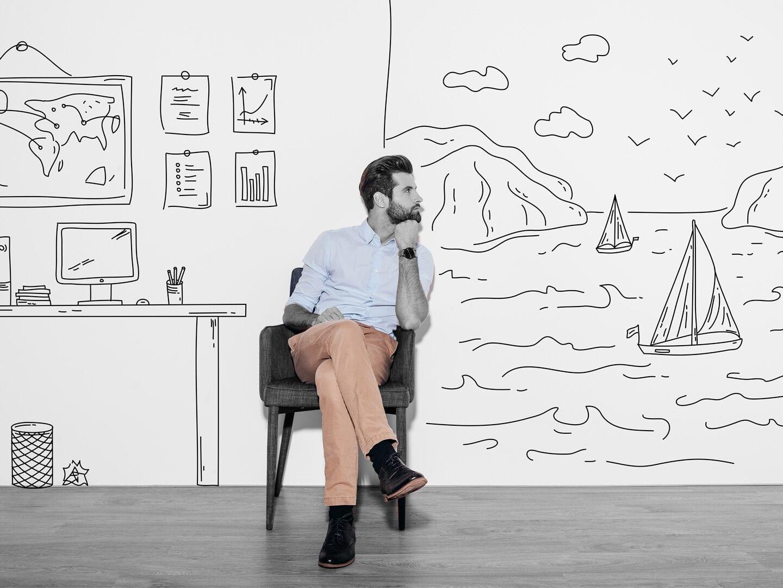 Ein Mann sitzt vor einem gemalten Hintergrund, uf dem ein Strand und ein Büro zu sehen sind.