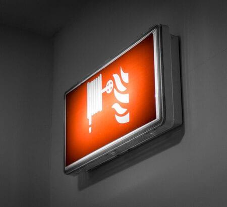 Ein beleuchtetes Schild weist den Weg zum Feuerlöscher.