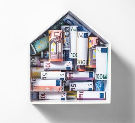 Eine Box in Hausform mit Geldscheinen