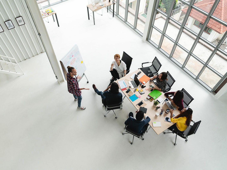Arbeitssituation in einem Start-up. Aus der Vogelperspektive ist ein Konferenztisch abgebildet, an dem mehrere Menschen arbeiten und einer Präsentation einer Kollegin folgen.