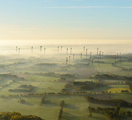 Blick über nebelverhangene grüne und flache Landschaft mit vielen Windrädern am Horizont