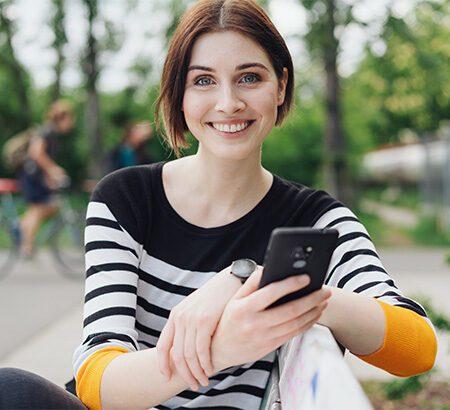 Junge Frau mit Smartphone in der Hand sitzt auf einer Bank auf einem Schulhof. Im Hintergrund sind Fahrradfahrer zu sehen.