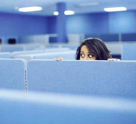 Frau die sich im Büro hinter einer Wand versteckt