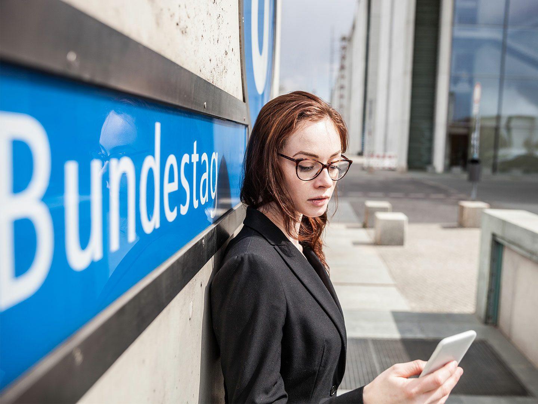 Frau mit Smartphone vor einer Berliner U-Bahnhaltestelle