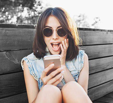 Eine Frau schaut überrascht auf ihr Smartphone.
