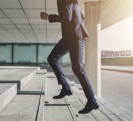 Mann in Anzug steigt die Treppe hoch